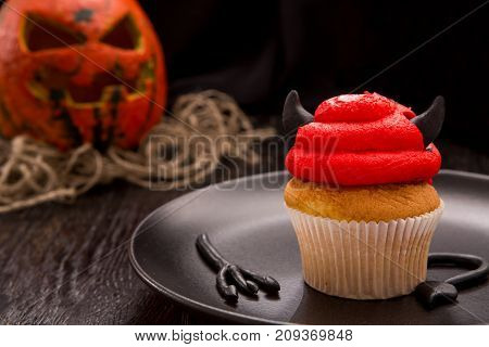 Halloween red one cupcake in the shape of the devil. Cupcake with horns and tail. Halloween decorated cookie on dark wooden table. Close up