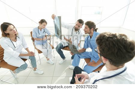 radiologists and a surgeon discussing a radiograph of a patient