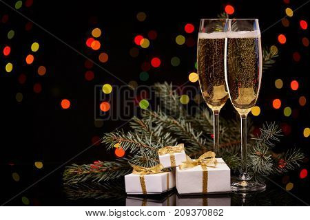 Two glasses with champange, fir tree branch, gift boxes on a black background with multi-colored lightes of garland.  New year and Christmas.