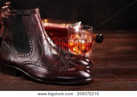 Brown Leather Chelsea Boots Polished With Glass And Bottle Whiskey Defocused.selective Focus. Waxing