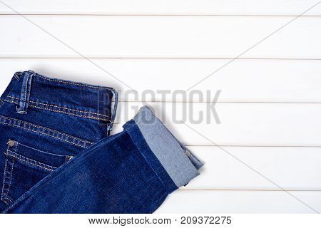 Blue jeans on a white wooden background
