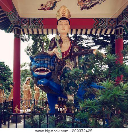 Hong Kong - October 2017: Sculpture of Manjushri on blue lion at Ten Thousand Buddhas Monastery.