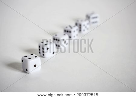 White dices in a row or scattered on white background soft focus