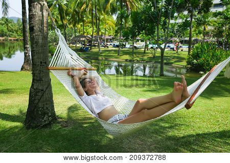 beautiful girl resting in a hammock at sunset