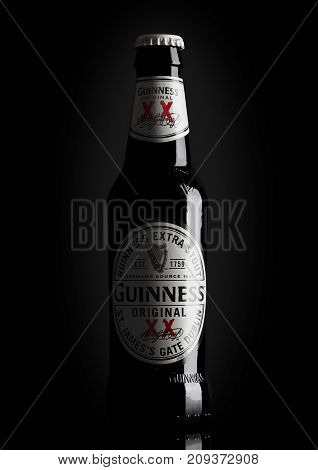 London, Uk - October 15, 2017: Guinness Extra Stout Beer Bottle On Black. Guinness Beer Has Been Pro