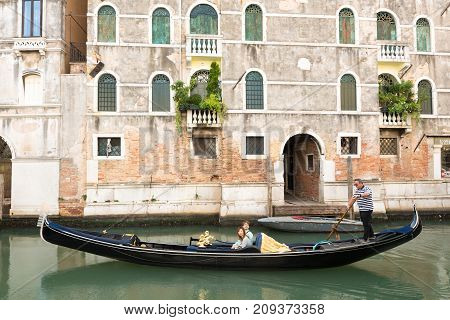Venice, Italy - September 29, 2017: A venetian gondolier is punting a gondola through the green canal waters of Venice, Italy