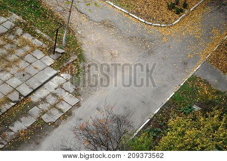 Top view of an old yard road covered by fallen autumn leaves. Autumn mood.