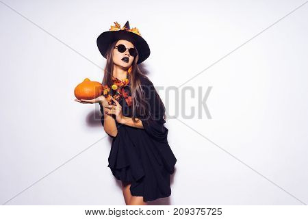 a young gothic bitch girl in sunglasses changed into a witch for halloween, holds a pumpkin in her hands