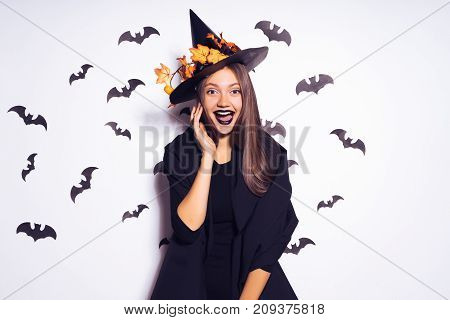 young laughing girl with black lipstick in the form of a witch for halloween
