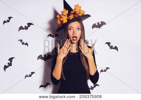 a young surprised gothic girl in a black witch hat, celebrates halloween. against the background of drawings of bats