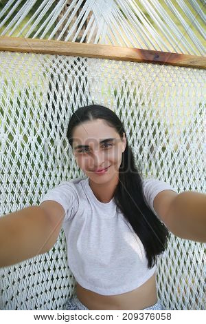 Woman Lying On Hammock And Making Selfie Photo On Smartphone Outdoors