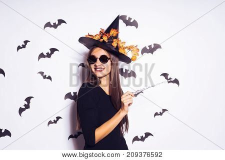 A young gothic girl dressed in a witch for Halloween, conjures