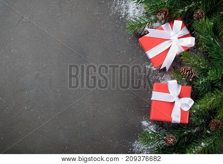 Two christmas gift boxes on the right side of a dark stone background fir branches ans cones snowflakes copy space top view