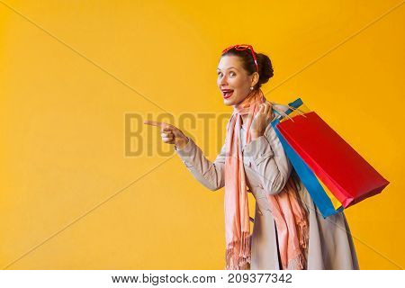 Young Adult Woman Pointing Finger On Copy Space And Looking At Camera And Toothy Smile. On Yellow Ba