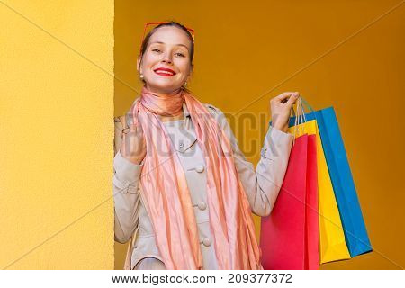 The Beautiful Bun Haired Woman In Casual Clothing With Shopping Bags, Looking At Camera With Smiling