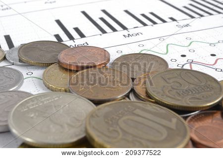 Financial background with different coins and graph.