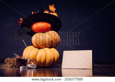 autumn holiday, a large pumpkin, golden leaves on a black witch hat,candles, dry grass, cardboard box   Halloween, a mesmerizing picture