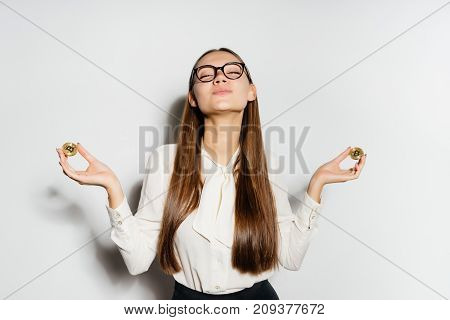 nice happy girl  looks at the camera and holds the gold coin and a bank card in his hands. Bitcoin, crypto currency