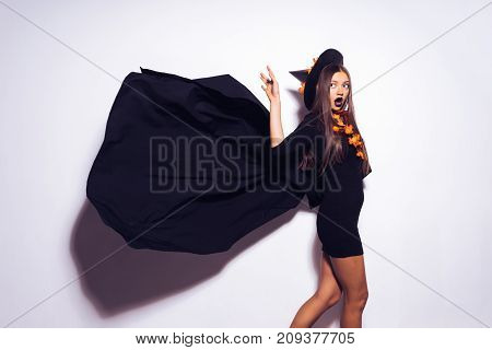 The witch in a beautiful black outfit and in a black hat is frighteningly looking into the camera, flying mantle, autumn holiday Halloween, Halloween party
