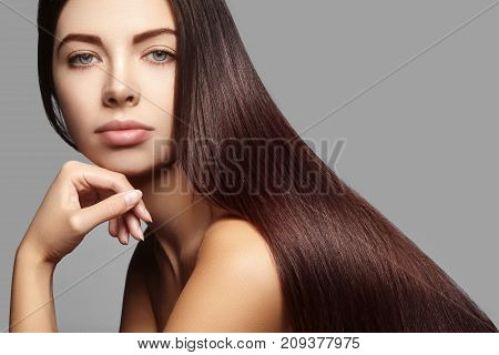 Beautiful yong woman with long straight brown hair. Sexy fashion model with smooth gloss hairstyle keratin treatment