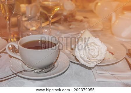 Hot tea in glass transparent Cup and a piece of cake decorated with a rose at the restaurant. The horizontal frame.