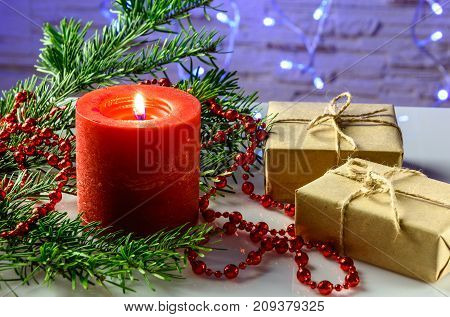 Christmas festive card with fir branches gift box and festive decor on the background with Christmas lights.