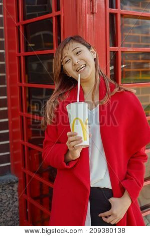 KALININGRAD, RUSSIA - CIRCA SEPTEMBER, 2017: outdoor portrait of pretty woman with McDonald's disposable paper cup.