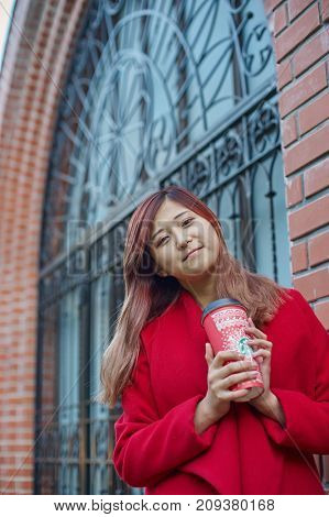 KALININGRAD, RUSSIA - CIRCA SEPTEMBER, 2017: outdoor portrait of pretty woman with Starbucks disposable paper cup.