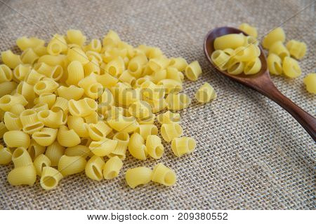 Ditalini raw pasta in wooden spoon on sack rustic background . Natural and healthy food concept