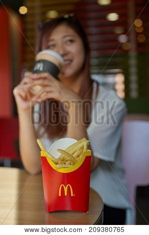 KALININGRAD, RUSSIA - CIRCA OCTOBER, 2017: pretty woman drink at McDonald's restaurant. McDonald's is an American hamburger and fast food restaurant chain.