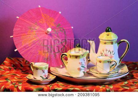 Miniature tea set and umbrella sitting on a multi-colored tablecloth.