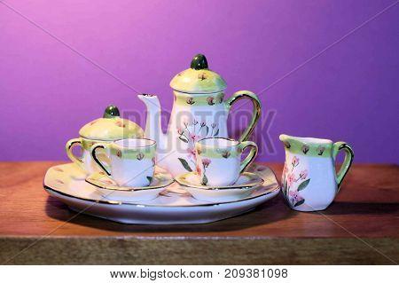 Miniature tea set sitting on a wooden table.