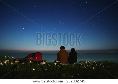 Couple With A Guitar On The Beach Under The Stars