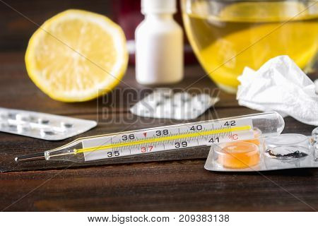 Glass mercury thermometer with a high temperature of 37.5 against the background of medicines lemon tea folk remedies tablets spray. Diagnosis of the disease. Treatment.