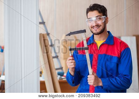 Young repairman carpenter working with clamps