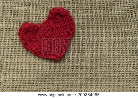 red knitted heart lies on a wooden board