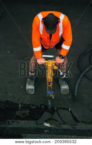 Road Worker With A Drill Breaking Up Asphalt On The Road