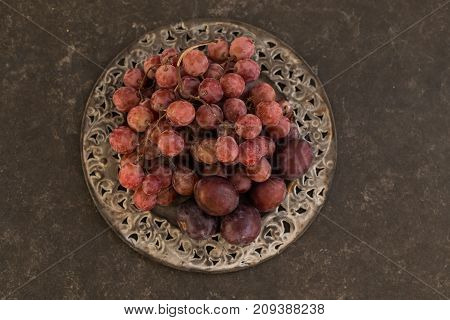 Upper top view shot of grapes and plums on iron vintage plate over dark gray rustic background