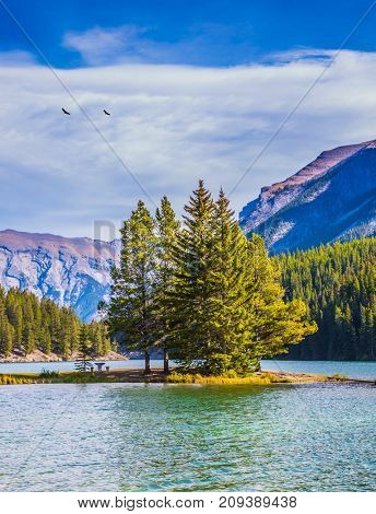 The concept of ecological and active tourist. Golden Autumn in the Rocky Mountains. The morning sun warms the picturesque lake and small island