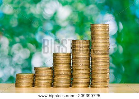Step Of Coins Stacks On Table In Garden With Green Background, Finance And Business Concept.