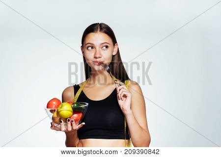 a young athletic girl wants to lose weight, holds a plate with useful vegetables and fruits in her hands