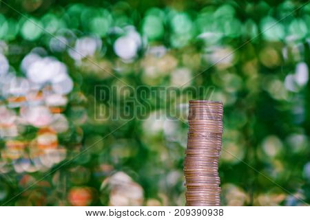 Stacks Of Coins On Table In Garden With Green Background, Finance And Business Concept.