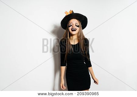 a young laughing girl dressed in a witch for Halloween, put on a big black hat