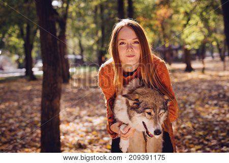 young red-haired girl posing in autumn park with her dog
