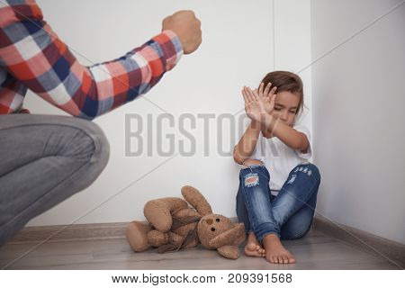 Man threatening his daughter at home. Domestic violence concept