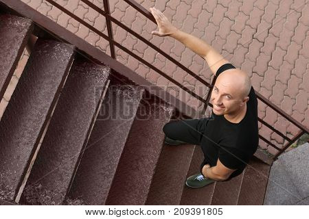 Bald man walking up stairs outdoors