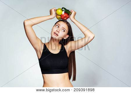 a young athletic girl looks upset, holds a plate with useful vegetables and fruits over her head