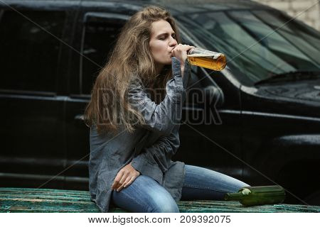 Woman drinking alcohol near car