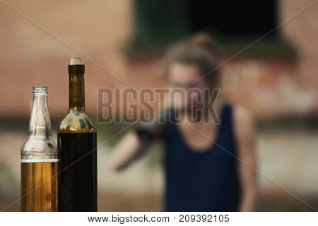 Bottles with alcohol on blurred view of drunk woman