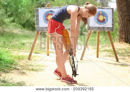 Young woman loading crossbow outdoors